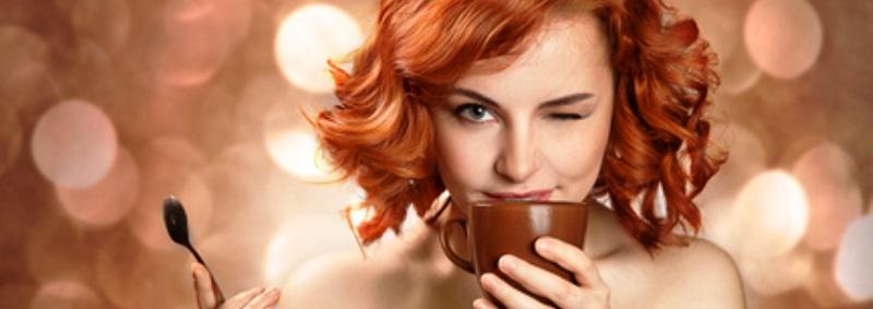 Красивая рыжеволосая девушка с чашкой кофе