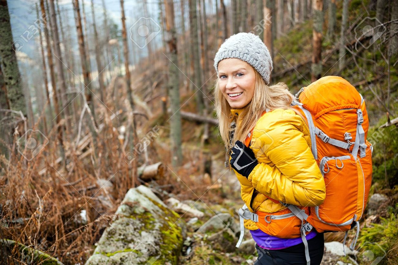 20439096-Woman-hiking-in-autumn-forest-in-mountains-Stock-Photo