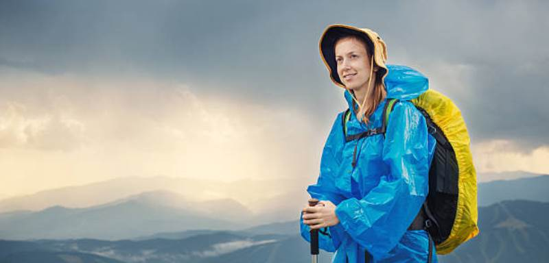 Woman with raincoat hiking in rainy weather